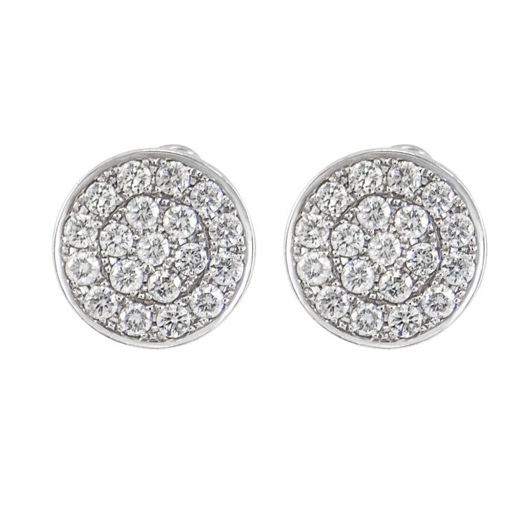 Charming and stylish these round disc earrings are pavé-set totaling 2.35 carats white diamonds (G-H color and SI1 clarity) crafted in 14 karat white gold. Approximate diameter is 15/8 inches. For security and ease of use the clasps are omega back