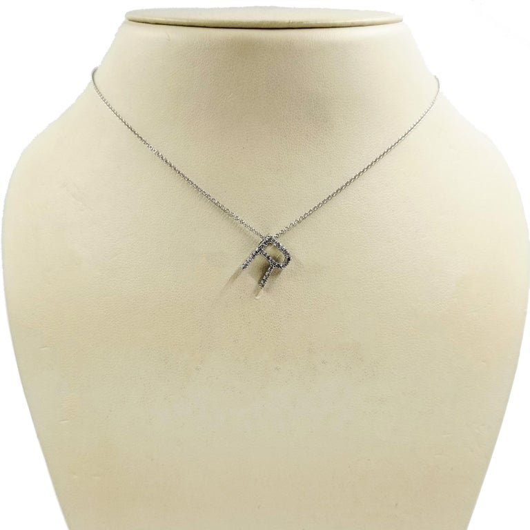 14 Karat White Gold Diamond R Initial Pendant on 16 Inch Chain. The Pendant Contains Round Single Cut Diamonds of I1 Clarity & H Color Totaling Exactly 0.11 Carats. Pendant Slides Freely on Chain.