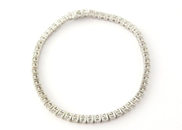 Vintage 14 Karat White Gold Diamond Tennis Bracelet 5.5 TCW  This exquisite tennis bracelet features 55 round brilliant cut diamonds set in classic 14K white gold. Width: 3.5 mm. Safety closure.  Approximate total carat weight: 5.5 TCW  Diamond