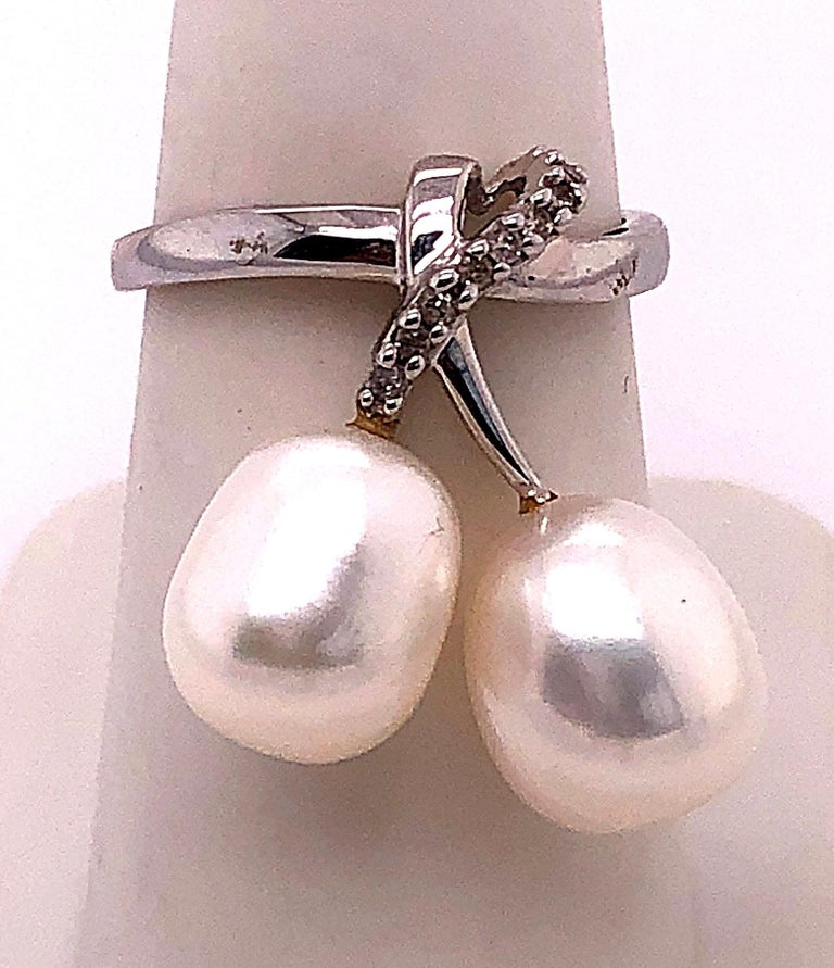 14 Karat White Gold Pearl and Diamond Free Form Ring 0.06 total diamond weight. 2 piece 9.5 mm pearls Size 7 2.04 grams total weight. Height: 25 mm Width: 22 mm