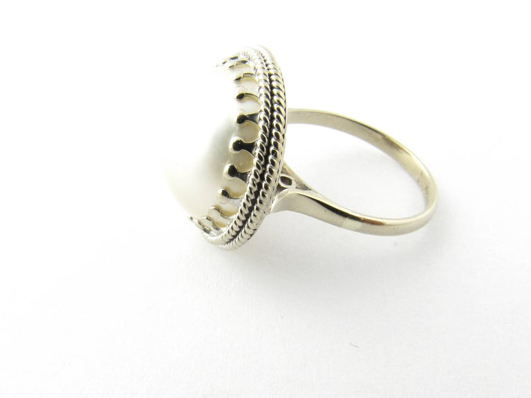 Vintage 14 Karat White Gold Pearl Ring Size 5.75-  This lovely ring features a stunning pearl (15 mm) framed in beautifully detailed 14K white gold. Top of ring measures 18 mm. Shank measures 2 mm.  Ring Size: 5.75  Weight: 3.7 dwt. / 5.9 gr.