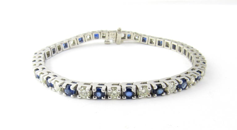 Vintage 14 Karat White Gold Sapphire and Diamond Bracelet  This stunning tennis bracelet features 22 round brilliant cut diamonds and 22 round genuine blue sapphires set in classic 14K white gold. Safety closure. Width: 3 mm.  Approximate total