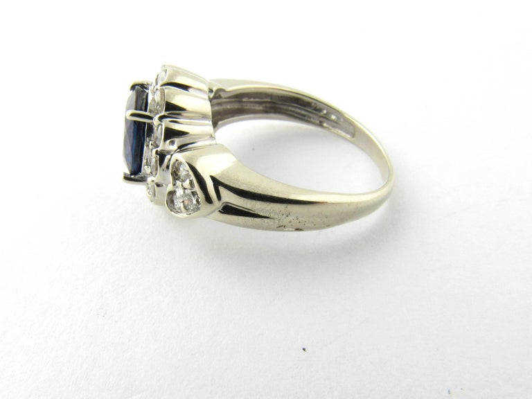 Vintage 14 Karat White Gold Sapphire and Diamond Ring Size 6.75-  This dazzling ring features one oval genuine sapphire (8 mm x 6 mm) surrounded by 18 round brilliant cut diamonds set in beautifully designed 14K white gold. Top of ring measures 12.5
