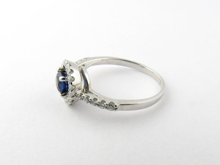 Vintage 14 Karat White Gold Sapphire and Diamond Ring Size 8.25-  This lovely ring features one genuine blue sapphire (.75 ct.) accented with 28 round brilliant cut diamonds set in beautifully detailed white gold.  Approximate total diamond weight: