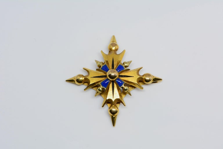 This pendant has blue enamelling that has been applied on top of 14 karat yellow gold. We believe it is in the form of a stylized maltese cross.  There is a spot on the back where you can thread a necklace through and wear it as a pendant. This