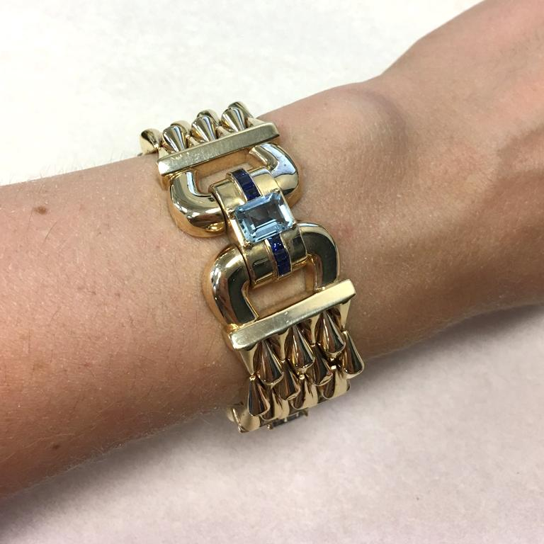 14Kt Yellow Gold Aquamarine & Sapphire flexible lady's Bracelet with a box clasp and a safety chain.  3 emerald cut cut aquamarines, total weight 4.80 cts measurements: 8.70x6.80x4.00mm  18 square blue sapphires  2.50mm  7