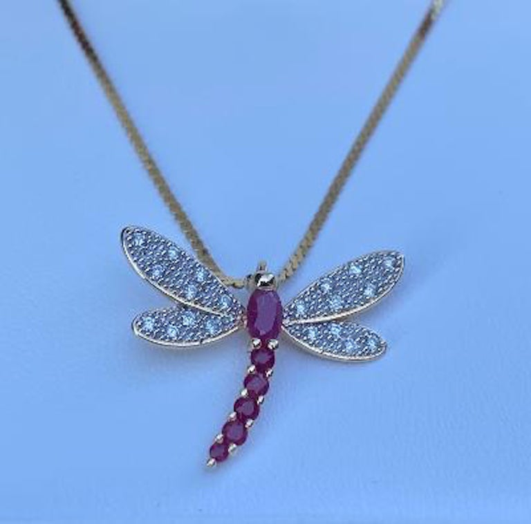 Ladies 14 Karat yellow and white gold ruby and diamond dragonfly pendant featuring six faceted red rubies making up the body of the dragonfly and 20 round brilliant diamonds are interspersed on the wings.  The beaded white gold wings shimmer with