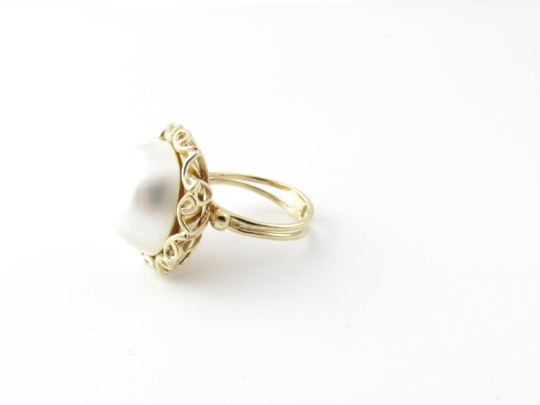 Vintage 14 Karat Yellow Gold Mobe Pearl Ring Size 7  This lovely ring features a stunning Mobe pearl (16 mm) set in beautifully detailed 14K yellow gold.  Top of ring measures 22 mm. Height: 14 mm. Shank: 4 mm.  Ring Size: 7  Weight: 5.6 dwt. / 8.8