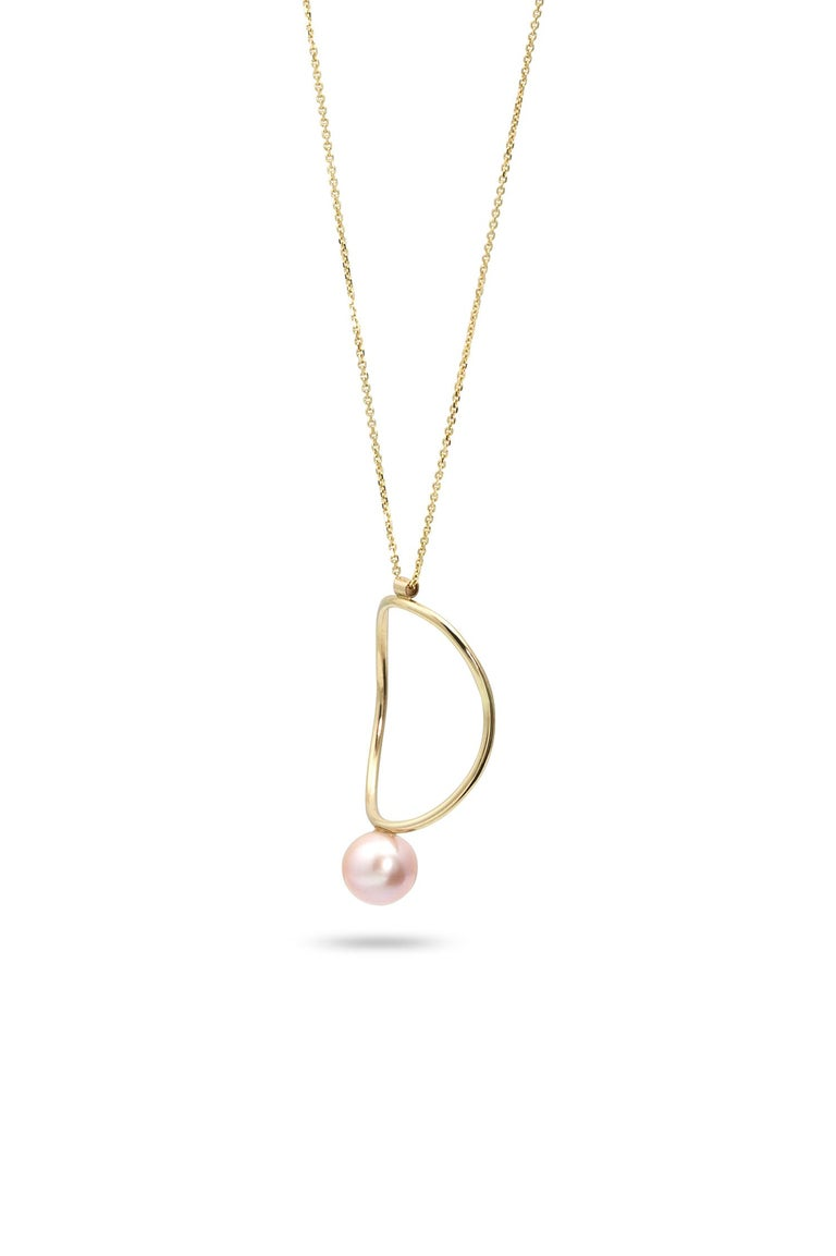 Strikingly minimal in its design, this 14k yellow gold necklace is as beautiful on bare skin as it is layered over a tee or lightweight turtleneck. The gentle curves of its hand-formed circle and single pink pearl remind us of our favorite