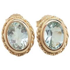 14 Karat Yellow Gold Oval Shaped Aquamarine Bezel Set Stud Earrings
