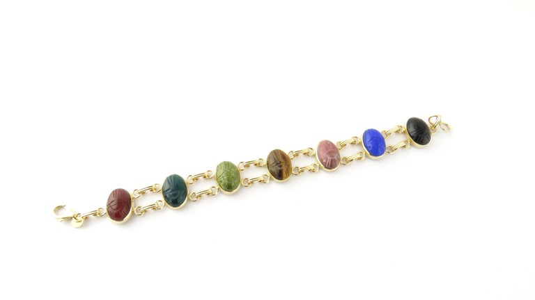 Vintage 14 Karat Yellow Gold Scarab Bracelet  This lovely scarab bracelet features seven oval semi-precious gemstones (14 mm x 11 mm); onyx, carnelian, tiger's eye, dark and light green marble, blue agate and quartz, set in classic 14K yellow