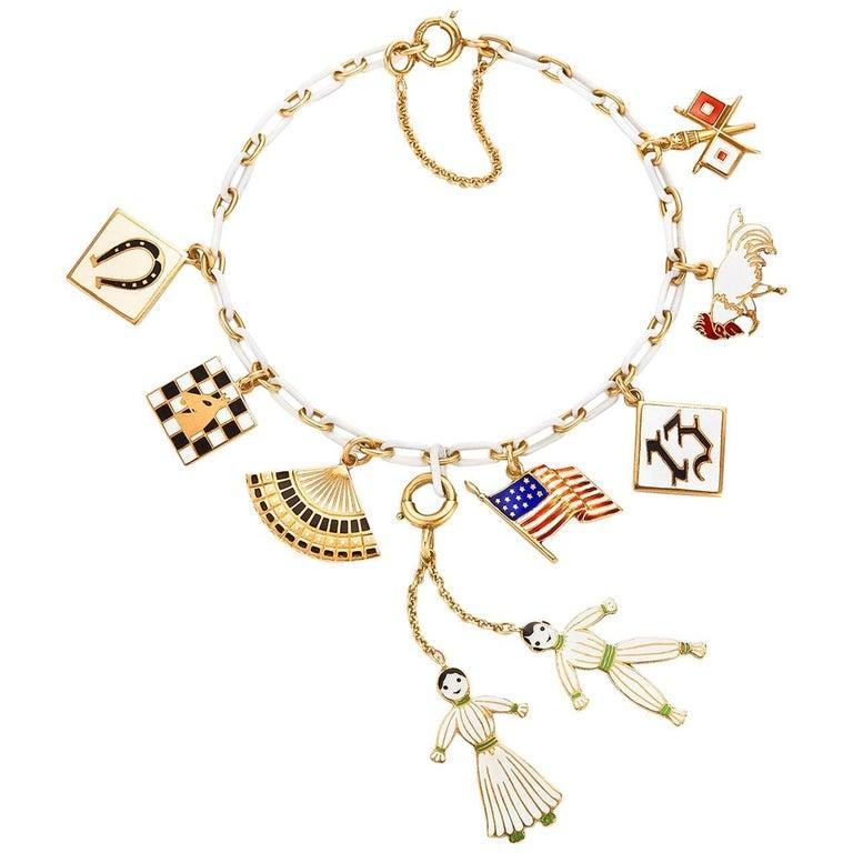Comprising eight enamel charms stamped 14K, the charms include a horseshoe plaque, a chess board, a fan, a pair of dolls, an American flag, a lucky 13, a rooster, and a pair of flags, 7x1/2x2     Signed Cartier