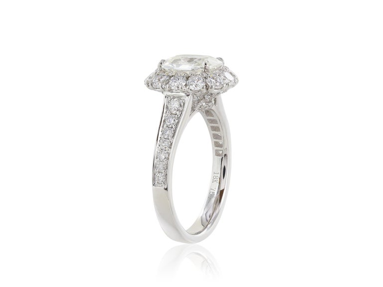 18 karat white gold ring consisting of 1 cushion cut diamond weighing 1.40 carats with a color and clarity of G/VS1 respectively set in a halo setting with round brilliant diamonds weighing 1.14 carats.