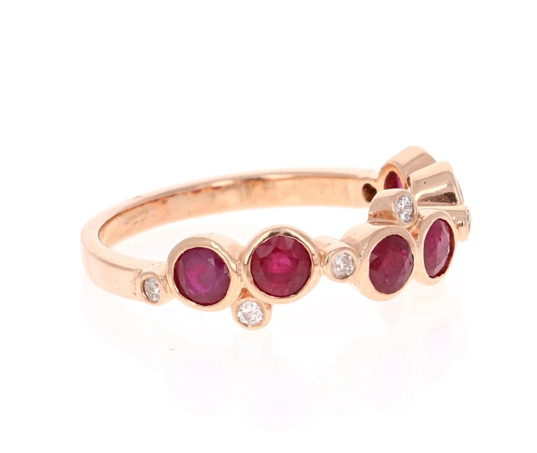This unique band has 6 floating Round Cut Rubies that weigh 1.30 Carats and 7 Round Cut Diamonds that weigh 0.10 Carats.   The ring is casted in 14K Rose Gold and weighs approximately 2.6 grams.   It is a size 7 and can be re-sized at no additional
