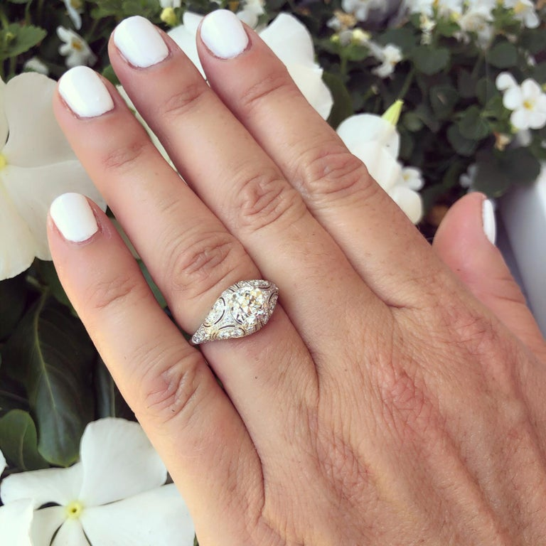 Inspired by the designs of the Belle Epoque, the platinum engagement ring features an old European-cut diamond weighing 1.41 carats, J-K color and SI clarity, set in a delicately pierced and domed custom French mounting set with 44 round