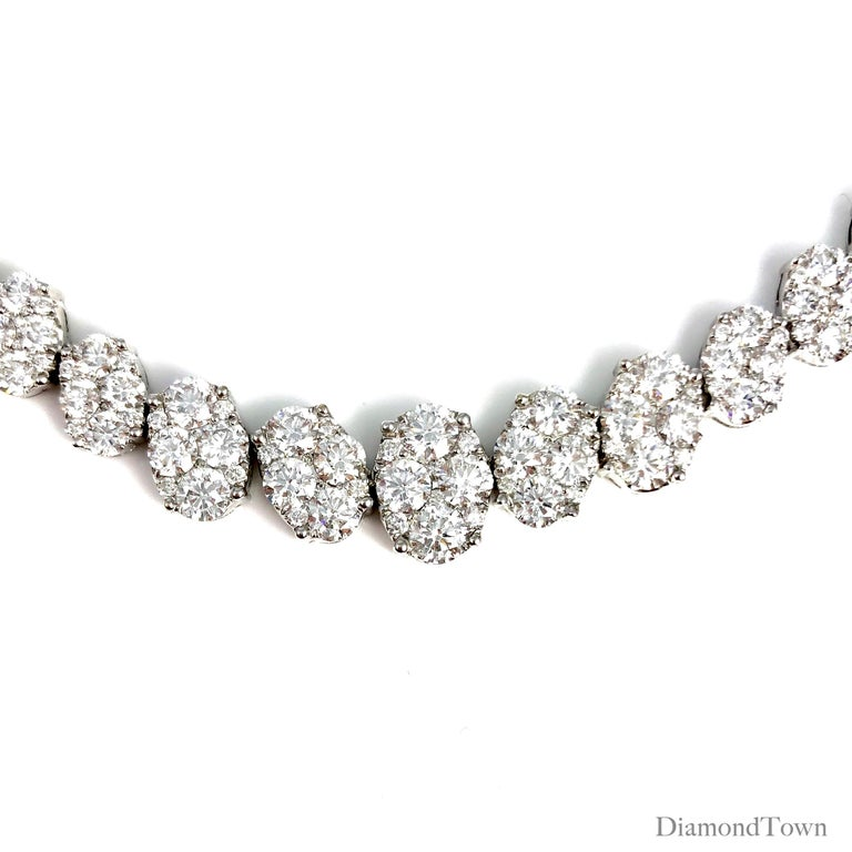 This stunning necklace holds 14.14 carats round white diamond clusters, arranged in ovals. The diamonds are set along the full length of the necklace, which closes securely by click lock and two side clasps.  Set in 18k White Gold.  Many of our