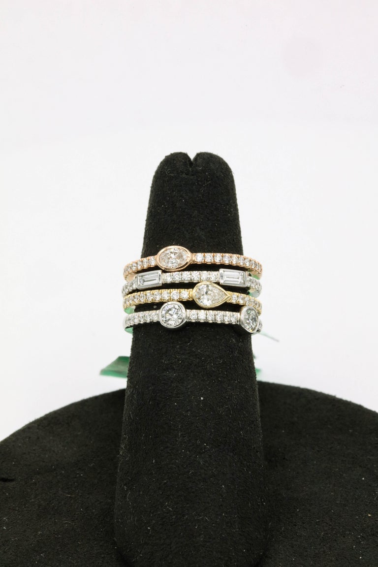 Diamond stackable rings featuring: One Oval diamond, 0.15 carats, 20 round brilliants, 0.20 carats, 14k rose gold One Pear diamond 0.17 carats, 20 round brilliants, 0.20 carats, 14k yellow gold Two Baguette diamonds, 0.14 carats, 18 round