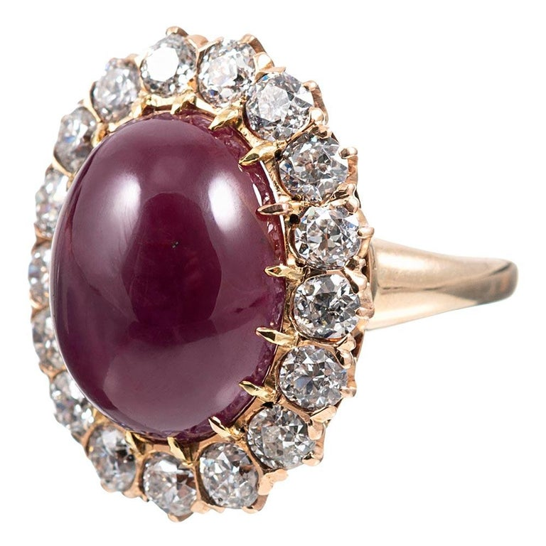 This charming cluster ring is set in the center with a 14.20 carat cabochon ruby and framed in a border of brilliant white diamonds. The 14 karat rose gold mounting offers a soft hue, which is quite symbiotic with the color of the major center