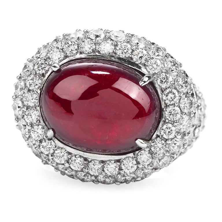 Sumptuous Deep Red Ruby in a Diamond Bed!  This Profound Colored Halo Design Cocktail Ring has a center 14.26 ct Oval Cabochon Ruby, prong set, It is crafted in solid 18K White Gold, and it is adorned by a Cluster Pave Style Round Cut Diamonds, with