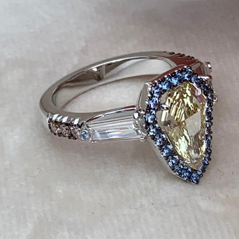 One of a kind handmade ring in 18K White gold 7,5 g. Set with a GIA certified Fancy Light Yellow Shield-Cut Diamond centerstone 1,43 carat., VVS2, Entourage pave set with Unheated Burma Blue Sapphires 0,345 ct. ( These Sapphires stay bright in the