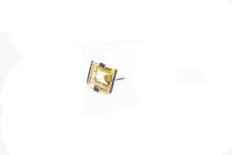 Gaston Ring A large platinum ring, showcasing a 14.38 carat square-cut lemon quartz.  The setting on this geometric ring is composed of four sides - two smaller rectangular motifs on the north and south side, and two large lines on the east and