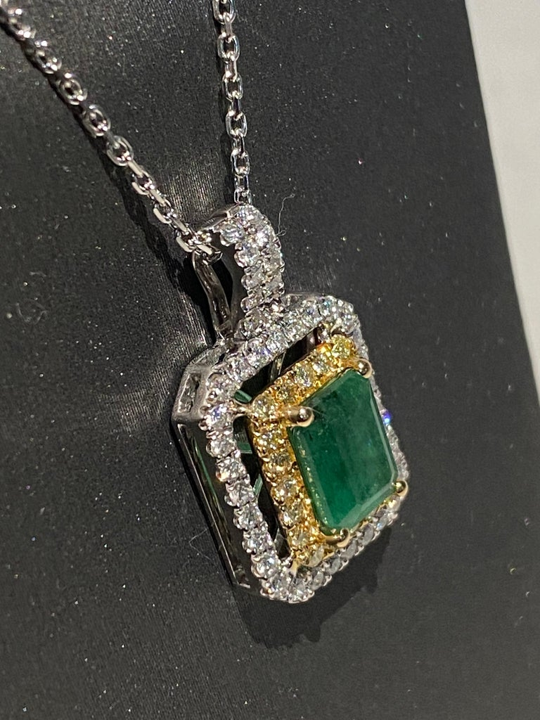 Emerald cut emerald has double halo of yellow and white diamonds. Double halo makes the center stone stand out and look bigger. Set in two tone gold, a white gold chain is included.  Emerald: 1.45ct White Diamond: 0.40ct Yellow Diamond: 0.22ct Two