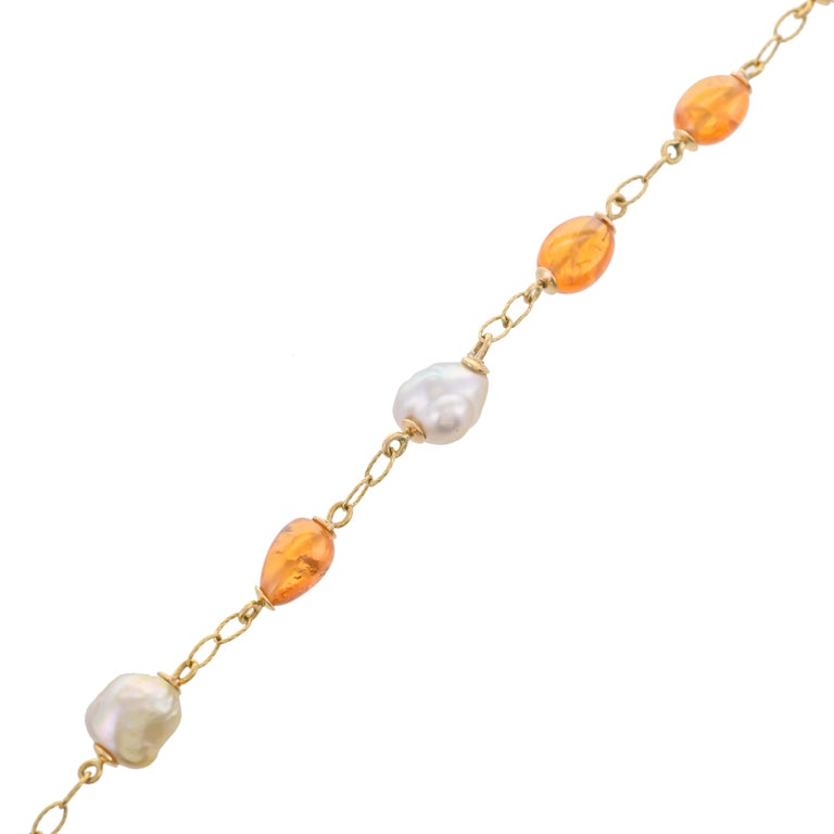 A stunning combination of 10.99 carats south sea pearls and 14.50 carats mandarin garnet. Further decorated with gold links adds gorgeousness to this 18 karats yellow gold bracelet. Length of bracelet- 8 inches
