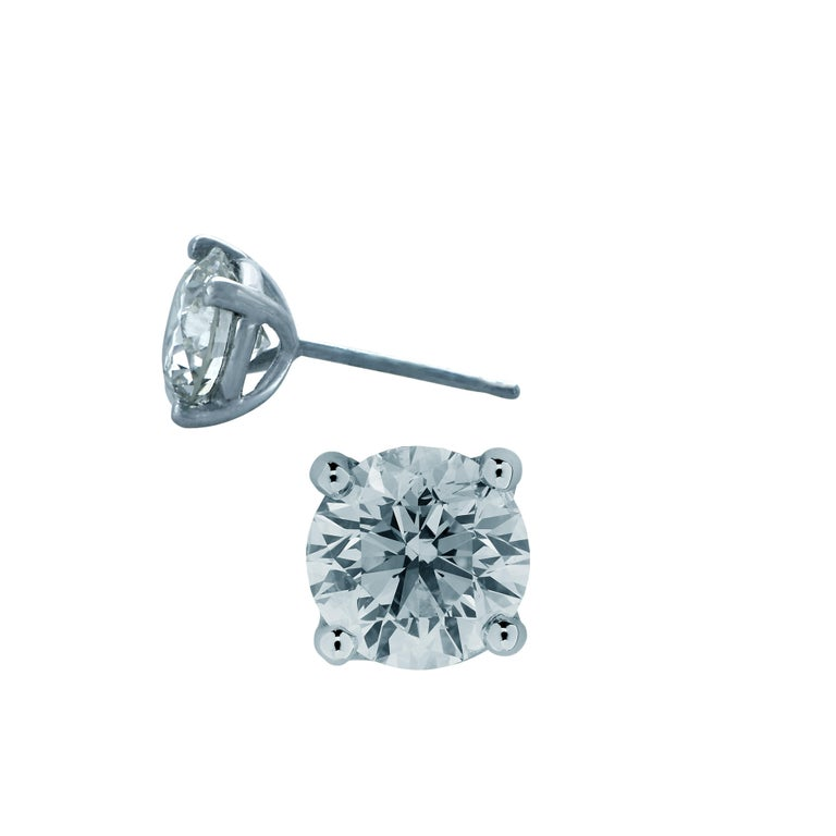 Stunning solitaire stud earrings crafted in 18 karat white gold, showcasing 2 round brilliant cut diamonds weighing 1.46 carats total, F color SI clarity. These gorgeous earrings are classic and timelessly elegant.  Our pieces are all accompanied by