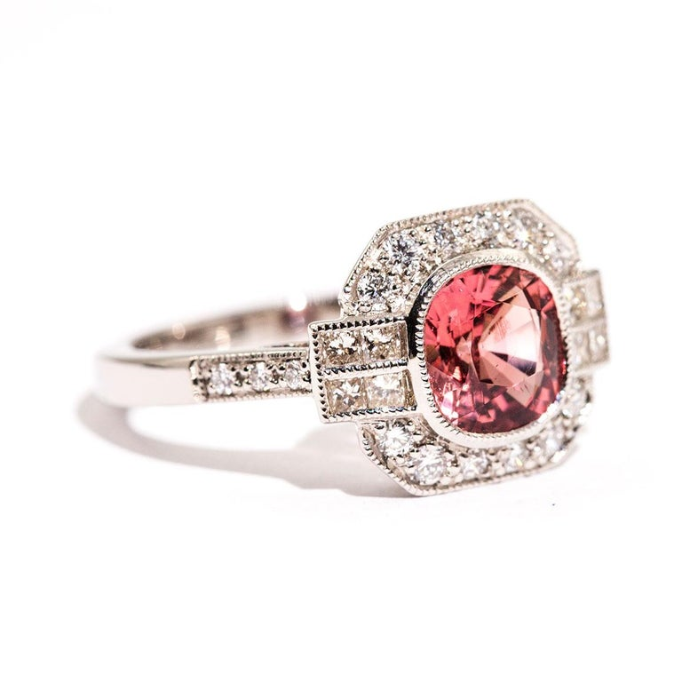Forged in platinum is this alluring Art Deco inspired ring that features a captivating 1.47 carat bright reddish orange cushion cut spinel complimented by a total of 0.52 carats of sparkling round brilliant cut diamonds. We have named this stunning