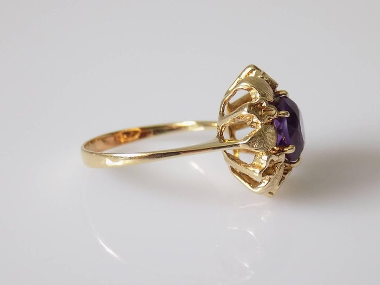 A lovely Vintage c.1950s 14 Carat Gold and Amethyst flower designed solitaire ring. Size L 1/2 UK, 6.25 US Height of the face 15mm. Amethyst 7mm. Weight 3.4gr. Unmarked, tested 14 Carat Gold.