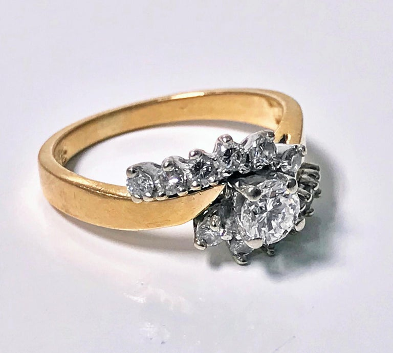 Diamond twist design 14K Ring. The ring centering a round brilliant cut diamond, approximately 0.30 ct, approximately VS1 clarity, approximately H colour, flanked with off set twist, set with 12 full cut diamonds, total diamond weight approximately