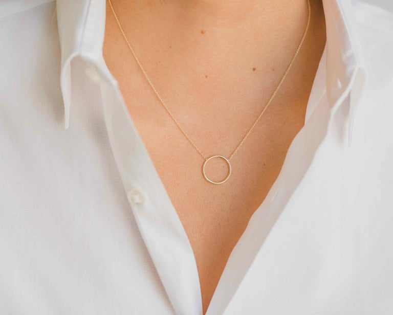 14K solid gold  circle ring necklace in 14k yellow gold. A simple, dainty and classic piece, sits beautifully by itself or layered, an everyday kind of necklace that will be your new obsession!  Made in L.A.  Size or ring/circle: Approx. 10mm