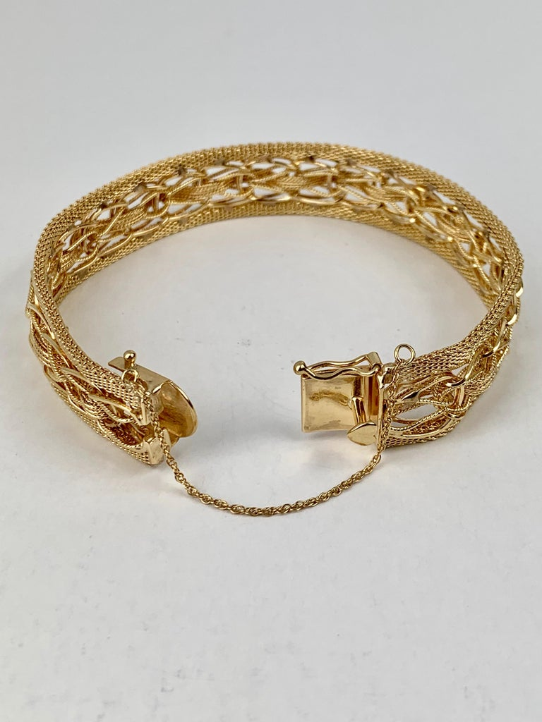 1950's solid 14 karat yellow gold mesh bracelet with heart shaped thumb catch plus a figure eight catch and safety chain on the side.  The mesh is quite interesting and partially hand woven.  The bracelet is clearly marked 14k on the back of the