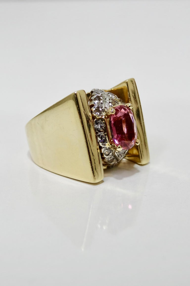 Elegant with a pop of color, this mid-20th century cluster ring is crafted from 14k Gold and features a thick tension band. Resting in the center prong setting is a stunning pink oval Tourmaline framed by a cluster of brilliant round cut diamonds.