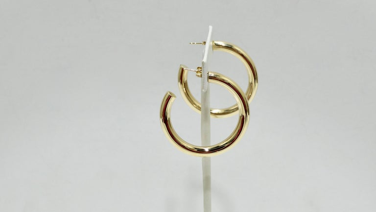 The perfect go-to earrings for your collection! Crafted from 14k gold, these thick banded gold hoops have pierced backs and are stamped 14k gold made in Turkey. Comes with original box and dust bag. Perfect to pair with all your Gucci, Chanel, and