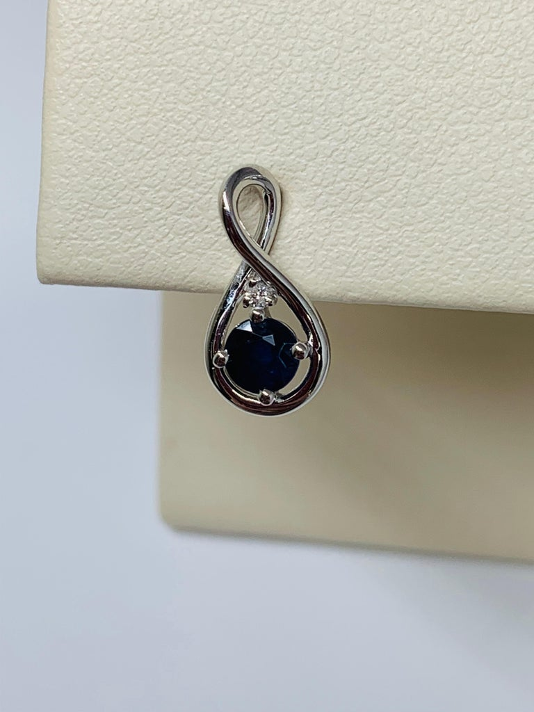 These 14K white gold dangle earrings are the perfect accessory for both everyday wear and special occasions! Each infinity shaped mounting holds a 0.34 carat round blue sapphire, for a total sapphire weight of 0.68 carats. The earrings also feature
