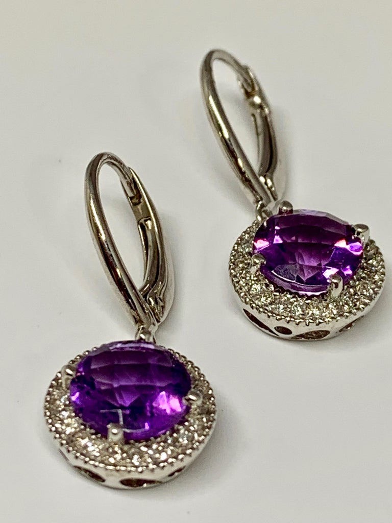 These 14K white gold lever-back earrings hold a 1.04 carat round checkerboard cut amethyst each, for a total amethyst weight of 2.08 carats. Surrounding each amethyst is a micro pave diamond halo holding 0.08 carats of round white diamonds each. The