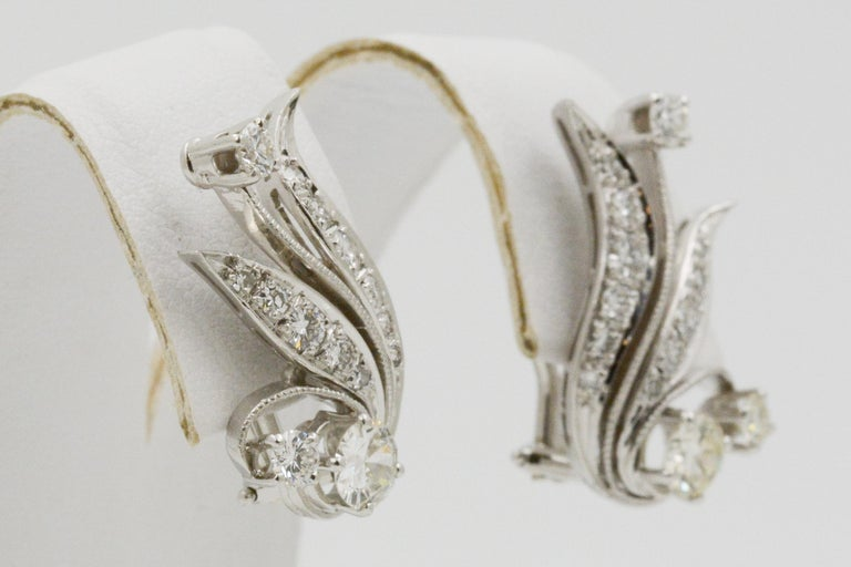 These earrings do not fall short of elegance and charm. 14k white gold and 28 round brilliant cut pave diamonds make up an intricate leaf design. The diamonds have a combined total weight of 1.50 carats with G-H VS. The earrings have omega clip post