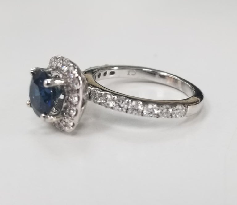 14k white gold blue sapphire and diamond halo ring, containing 1 round blue sapphire of gem quality weighing 1.50cts. and with 30 round full cut diamonds of very fine quality weighing .50pts. ring size is 6 and can be sized to fit for free.