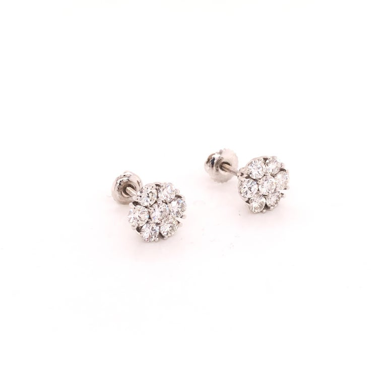A simple and elegant pair of cluster diamond floral earring studs contain 14 round-cut 10 pointer diamonds, set in 14K white gold.  Diamond weight ~ 1.40 carats