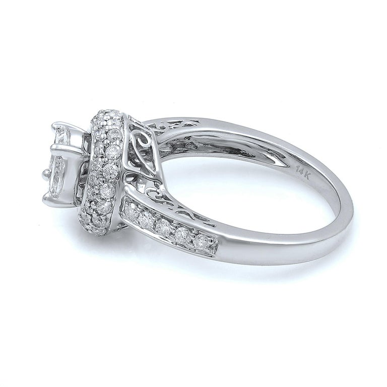 This elegant diamond engagement ring features 14k white gold with 1.13 carat brilliant round cut diamond. Center shaped as a round cut stone with 1 princess cut diamond  and 4 marquises. Halo and shank are set with little round cut diamonds. Prong