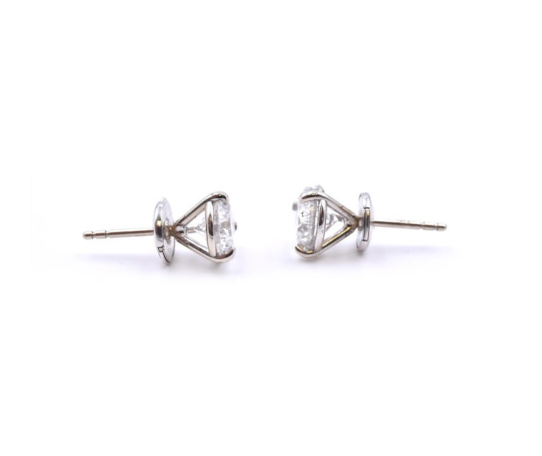 Material: 14k white gold Diamond: 1 round brilliant cut = 1.04ct Color: H Clarity: SI2 Diamond: 1 round brilliant cut = 1.00ct Color: H Clarity: SI1 Dimensions: earrings measure approximately 7.6mm Fastenings: post with la pousette backs Weight: