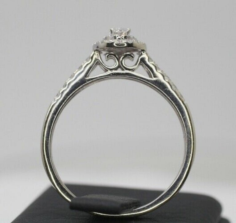 This beautiful Halo engagement ring is crafted in 14 karat white gold and features an oval-cut diamond at the center in H color and a clarity of SI1, surrounded by 43pcs of a halo round-cut diamonds, further adorned with round diamonds along its