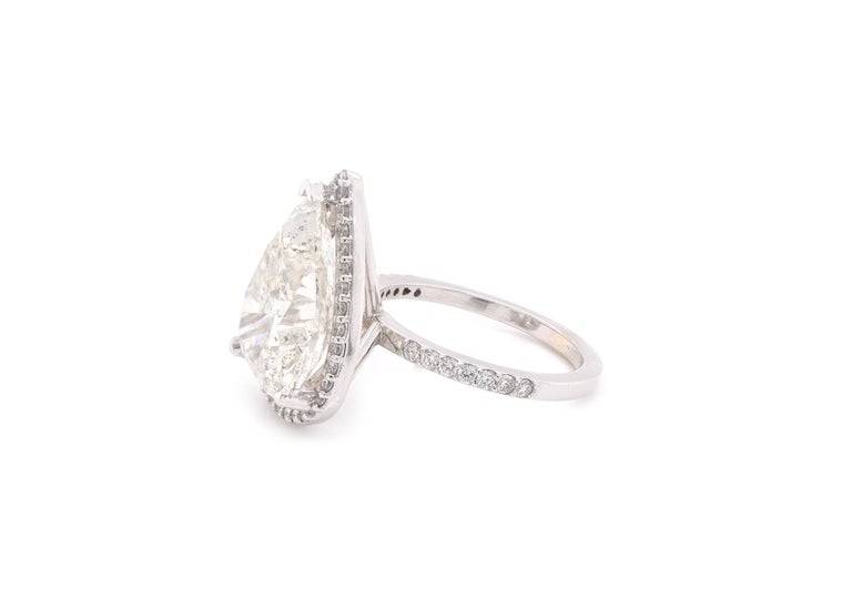 Material: 14k white gold  Center Diamond: 1 pear cut diamond = 10.09ct   Color: I Clarity: I1 Mounting Diamonds: 47 round brilliant cuts = 0.51cttw Color: G-H Clarity: VS2-SI1 Ring Size: 8 (please allow two additional shipping days for sizing