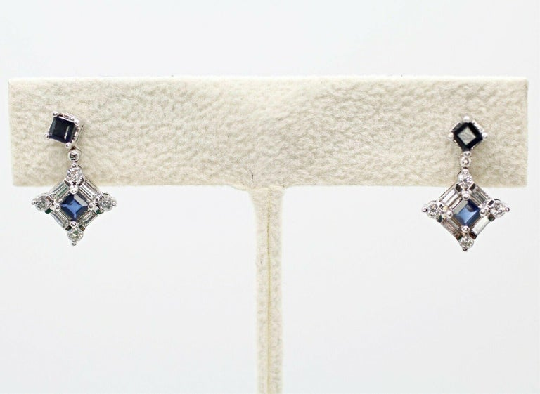 This elegant blue sapphire drop earrings features 8 pieces of round diamonds and 8 pieces of baguettes diamond. The earrings are crafted in a very classic design in 14k white gold.  Specifications:     main stone: 4 PIECES SAPPHIRE 0.50 CTW