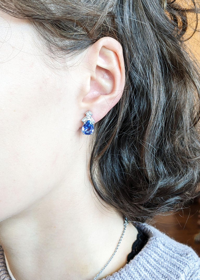 This is a gorgeous pair of stud earrings in 14k white gold with breathtaking pear-shaped purple and blue tanzanite centers. Each earring is accented with a square-cut diamond and two baguette diamonds that provide the perfect amount of sparkle to