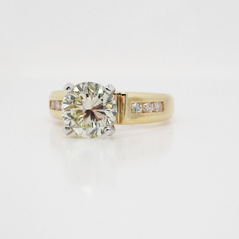 This is an absolutely stunning diamond engagement ring in 14k yellow gold with a breathtaking diamond center stone! This is a truly gorgeous diamond in a beautiful, traditional mounting. The center stone is flanked on either side by three delicate