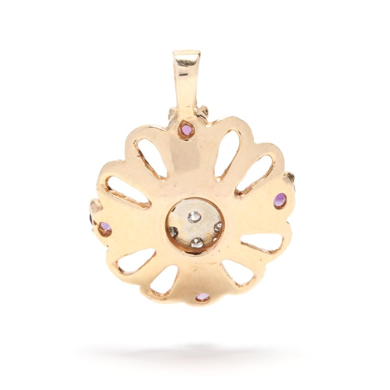 A 14 karat yellow gold, amethyst and diamond flower charm / pendant. This charm features an open flower motif with four prong set, round cut amethysts and a center cluster of full cut round diamonds weighing approximately .16 total