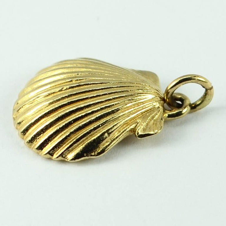 A 14 karat (14K) yellow gold charm pendant designed as a clam shell. Stamped 14K for 14 karat gold and American manufacture with an unknown makers mark.  Dimensions: 2.3 x 1.6 x 0.3 cm Weight: 4.10 grams