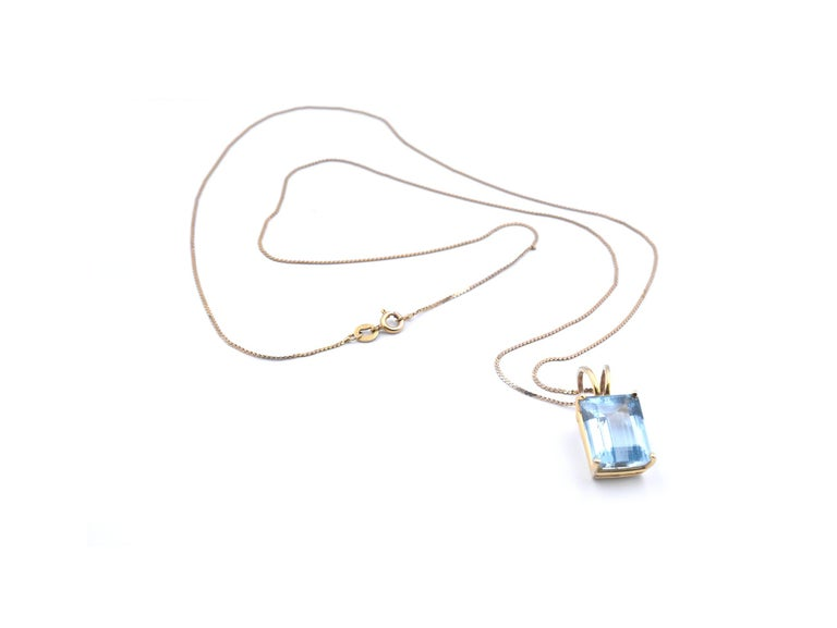 Designer: custom designed Material: 14k yellow gold Aquamarine: 1 emerald cut aquamarine = 9.63ct Dimensions: necklace is 23-inches in length and pendant measures 26mm x 12.40mm Weight: 6.57 grams